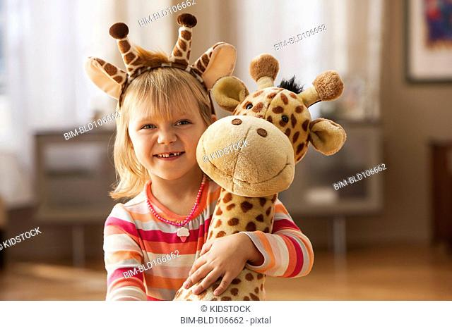 Caucasian girl wearing giraffe headband and holding toy giraffe
