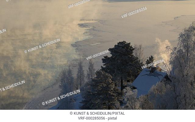 Clouds of steam are rising over the freezing river Ångermanälven on a very cold winter day while smoke is curling from a chimney