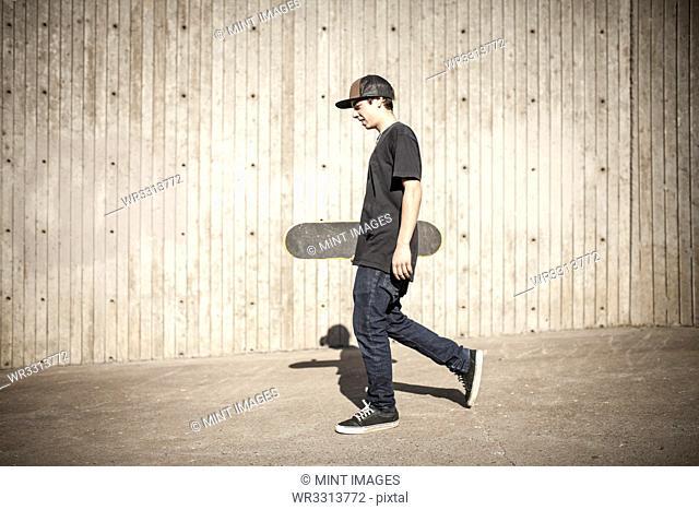 Caucasian man carrying skateboard near wooden wall