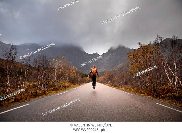 Norway, Lofoten Islands, man jumping on empty road surrounded by rock face