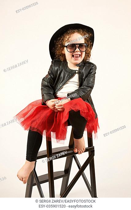 Little girl with black hat sitting on a high stool and dabbles