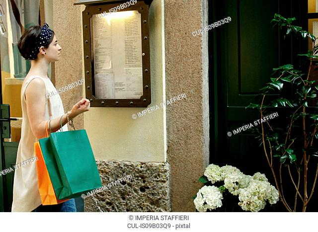 Woman with shopping bags reading menu outside restaurant, Milan, Italy