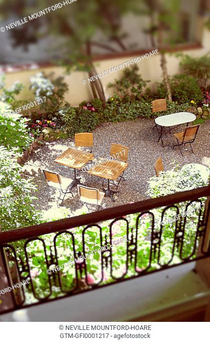 View from Paris hotel room overlooking tables in courtyard garden