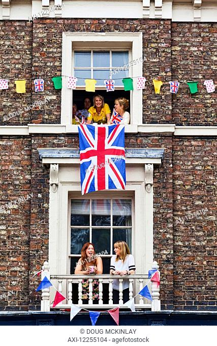 Spectators in windows waiting for the Tour de France; York, England