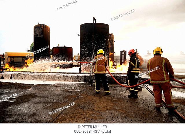 Firemen training, spraying firefighting foam onto oil storage tank fire at training facility