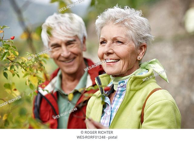 Portrait of happy senior woman with partner in the background