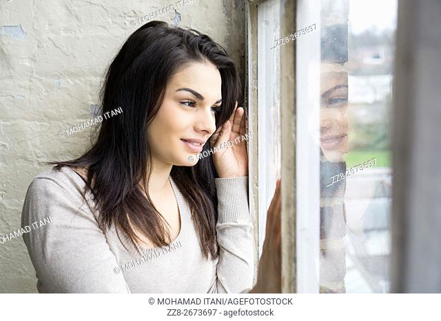 Happy young woman looking out of the window smiling