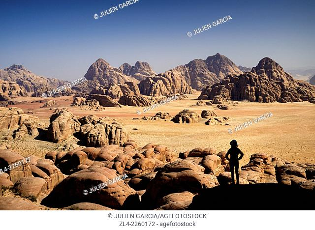 Silhouette of a woman contemplating the landscape from the mount Jebel Burdah. Jordan, Wadi Rum desert, protected area inscribed on UNESCO World Heritage list