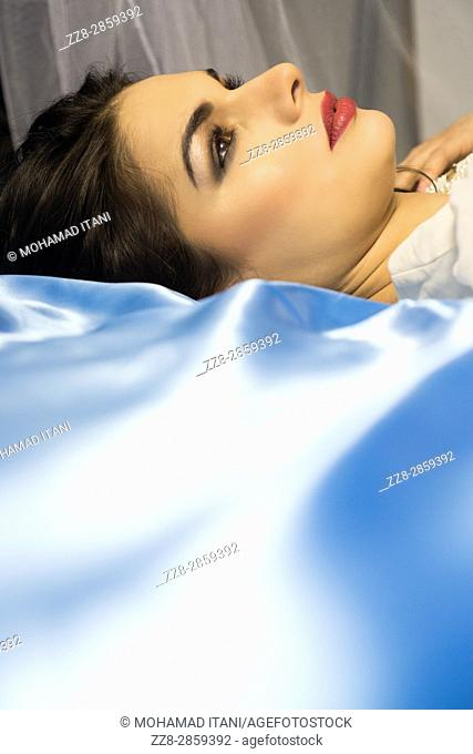 Thoughtful young woman laying down in bed looking up