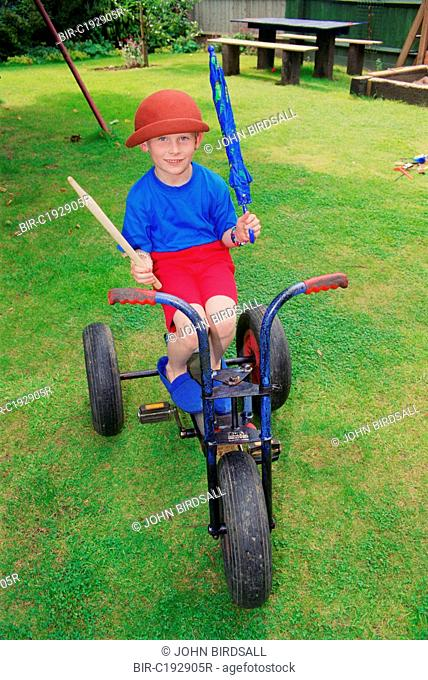 Young boy with autism sitting on tricycle in garden