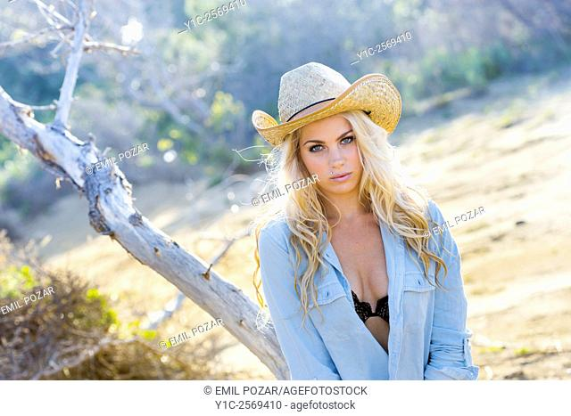 Stunning blonde countrygirl in denim shirt before tree