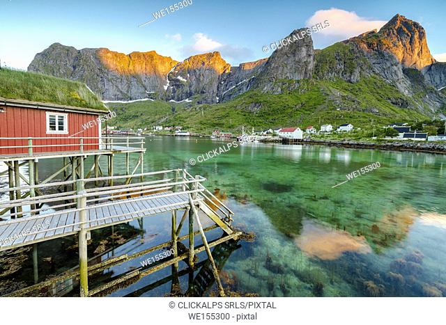 Midnight sun on fishing village and peaks surrounded by clear sea Reine Nordland county Lofoten Islands Northern Norway Europe