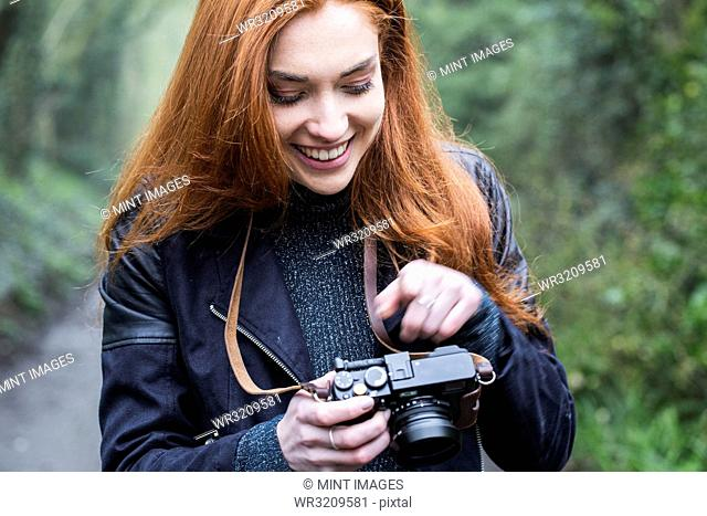 Smiling young woman with long red hair walking along forest path, taking pictures with vintage camera