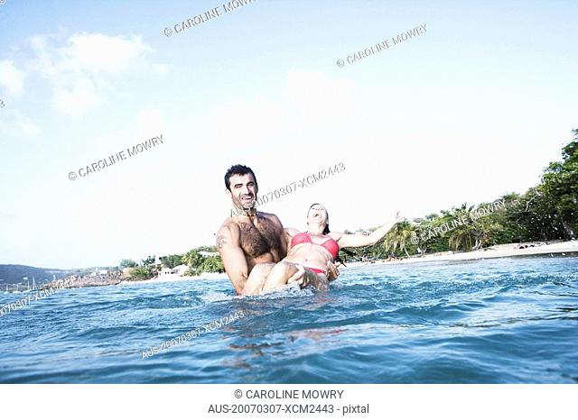 Mid adult man carrying a mid adult woman in water