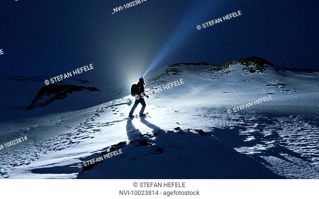 Snowshoe hiker at night with headlamp, Iceland, Scandinavia, Europe