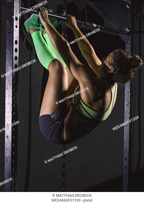 Young woman exercising at power rack