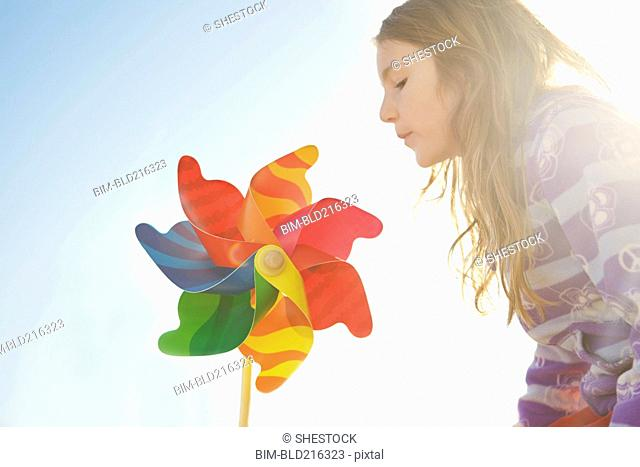 Caucasian girl playing with pinwheel under blue sky