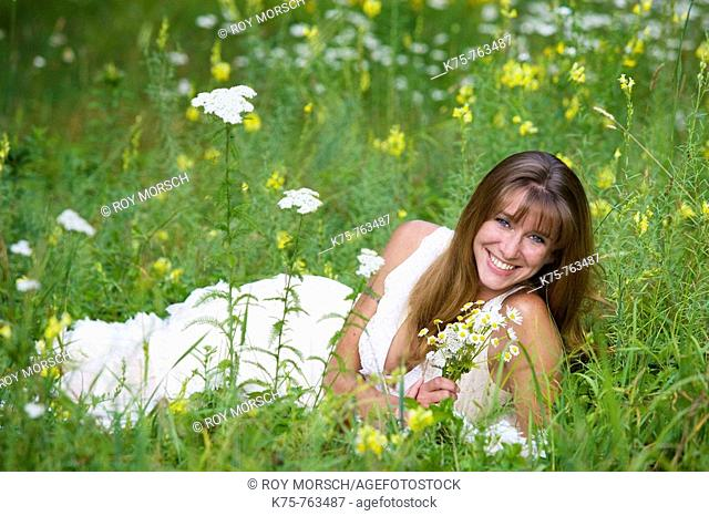 Woman with wildflower bouquet in meadow