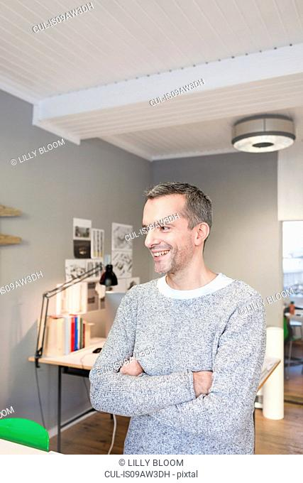 Mature man in office arms crossed looking away smiling
