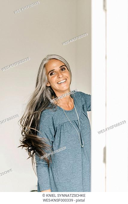 Portrait of smiling woman tossing her long grey hair