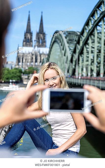 Germany, Cologne, young man taking a picture of his girlfriend with smartphone