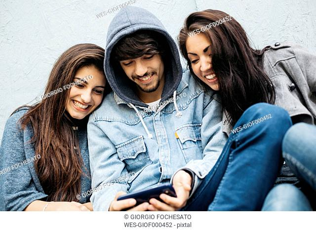 Three friends outdoors looking at cell phone