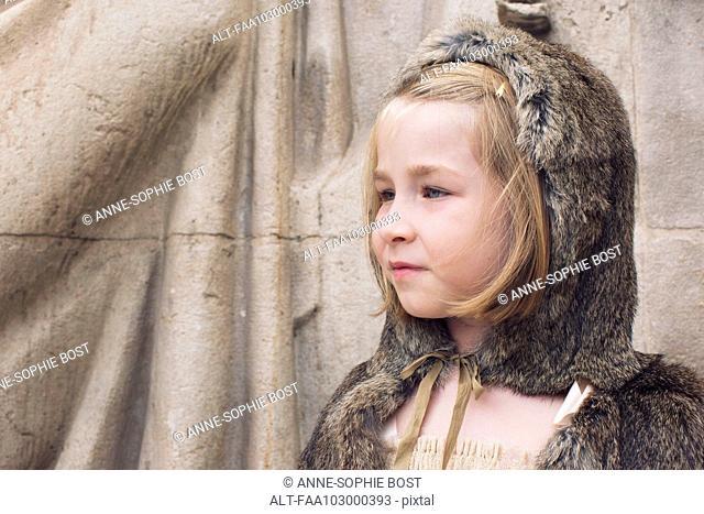 Little girl wearing hooded fur cloak outdoors, portrait