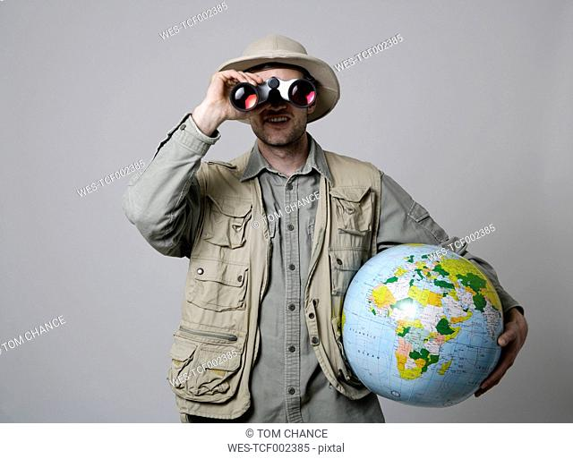 Young man looking through binocular and holding globe against white background