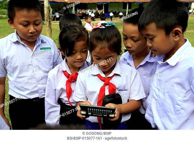 Elementary school. Lao schoolchildren playing a video game