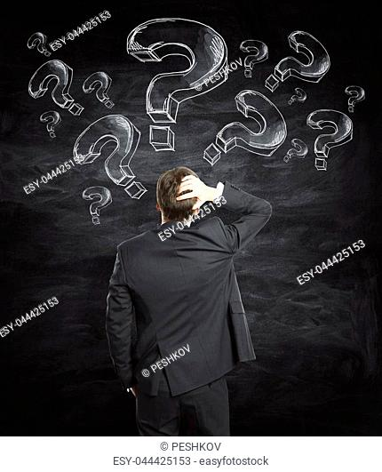 Thooughtful young businessman with question marks standing on chalkboard background. Confusion and faq concept