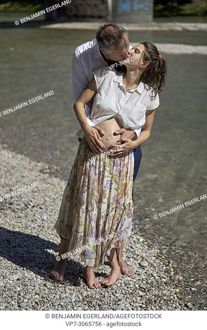 Couple kissing, pregnancy, age difference. At river Isar, Munich, Germany