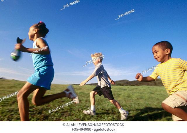 Three kids running in grassy park