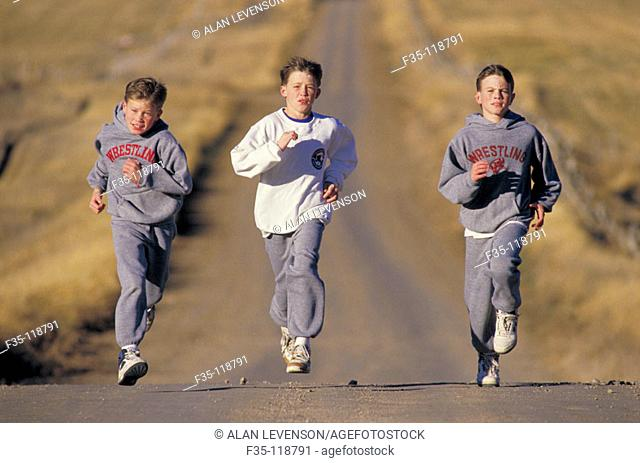 Boys running down country road