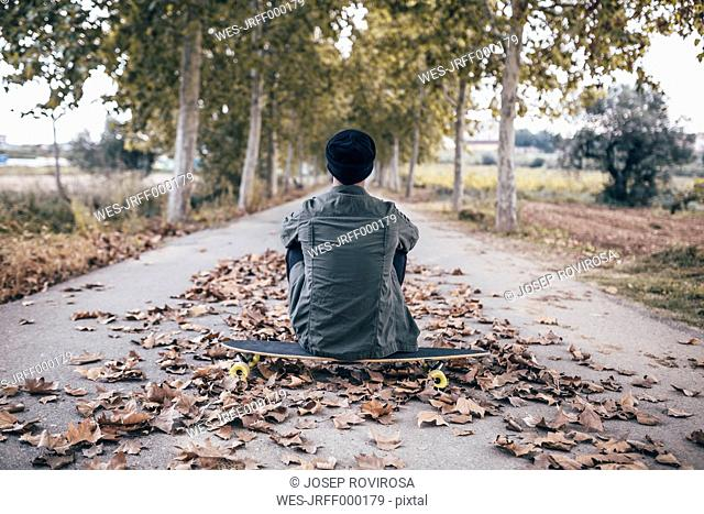 Spain, Tarragona, back view of young man sitting on longboard on autumnal country road