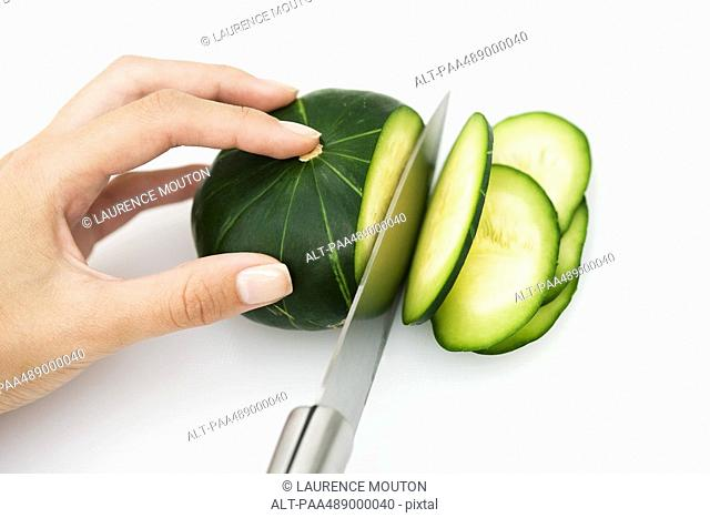 Woman slicing squash with knife, cropped view of hand