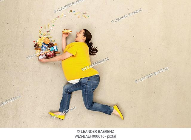 Woman eating food against beige background