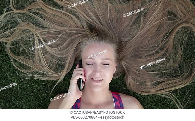Girl with beautiful blonde hair lying on grass