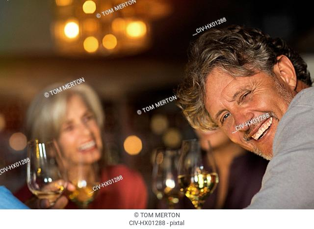 Portrait laughing senior man drinking white wine with friends at bar