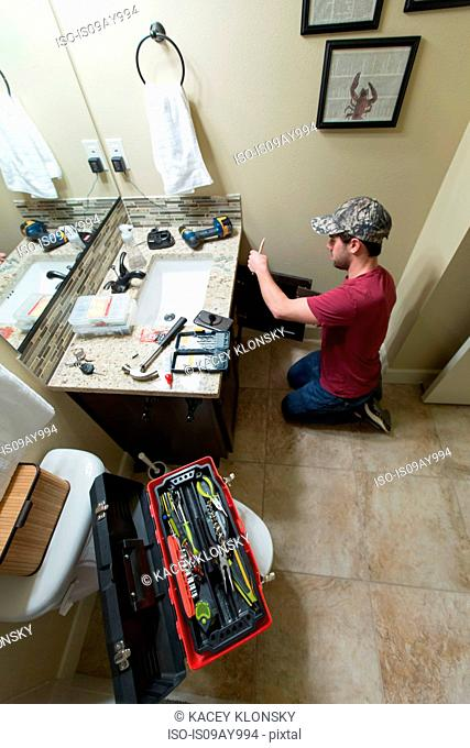 Man with toolbox kneeling to repair bathroom