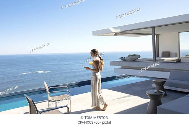 Woman walking and texting with smart phone on sunny modern, luxury home showcase patio with ocean view