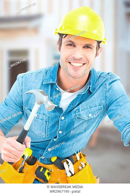 Carpenter with hammer on building site