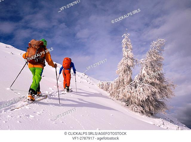 Two skiers touring in the sunlight after a snowfall, Cima della Rosetta, Valgerola, Italy, Alps