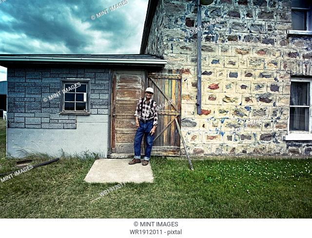 A farmer leaning against a doorjamb