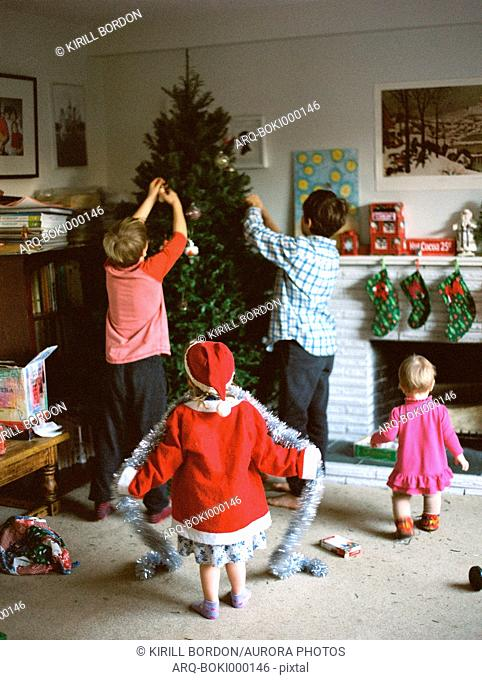 Rear view of group of four children decorating Christmas tree
