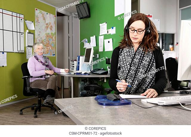 Two employees at work in an emergency responce center of a hospital, taking calls from patients
