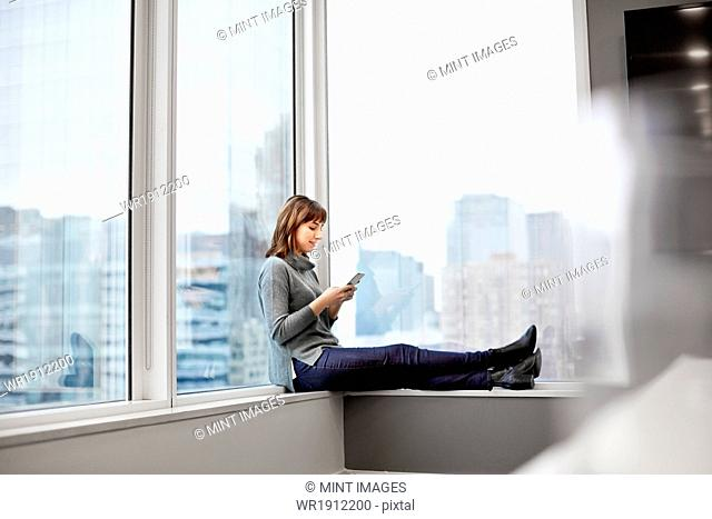 A woman holding a smart phone, sitting on a window ledge
