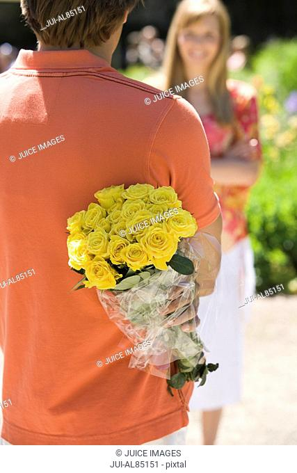 Man holding bouquet of flowers behind back and looking at girlfriend outdoors