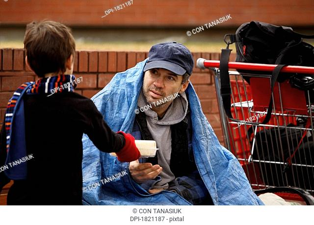Boy giving food to a homeless man