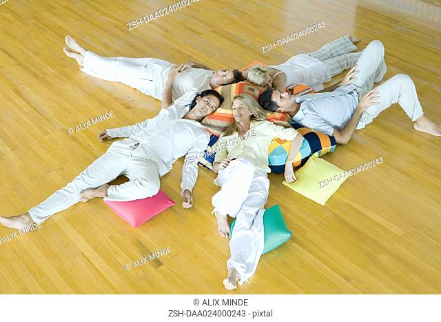 Group of adults lying on floor with cushions, high angle view