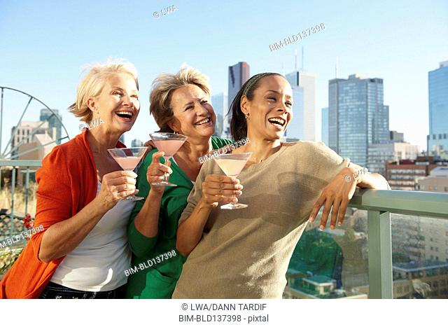 Women having drinks together on urban rooftop